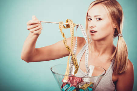 Photo pour Diet, healthy food, weight loss and slim body concept. Fit fitness girl holding bowl eating colorful measuring tapes - image libre de droit