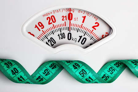 Foto de Dieting weightloss slim down concept. Closeup measuring tape on white weight scale - Imagen libre de derechos