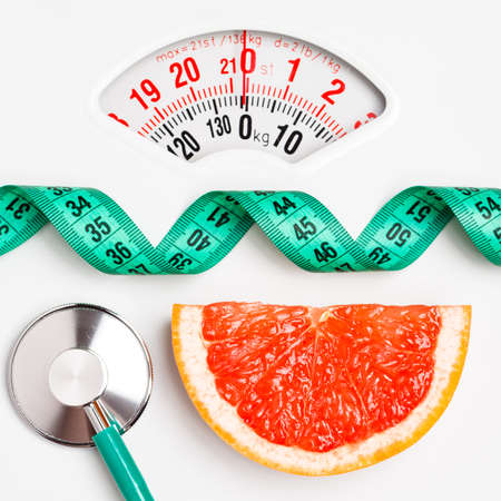 Foto per Diet healthy eating weight control concept. Grapefruit with measuring tape and stethoscope on white scales - Immagine Royalty Free