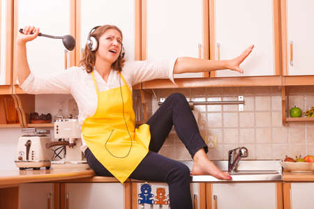 Photo for Relax in kitchen. Listening music singing and dancing. Funny happy housewife cook chef with earphones wearing yellow apron sitting and relaxing at home. - Royalty Free Image