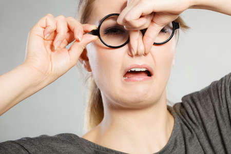 Photo pour Bad smell concept. Young woman feels disgust pinches her nose with fingers because of odor stench unpleasant stink. Facial reaction. - image libre de droit