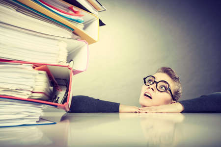 Photo for A lot of work and overwork concept. Terrified young businesswoman secretary with huge stack of binders. Scared accountant surrounded of to much work to do. - Royalty Free Image