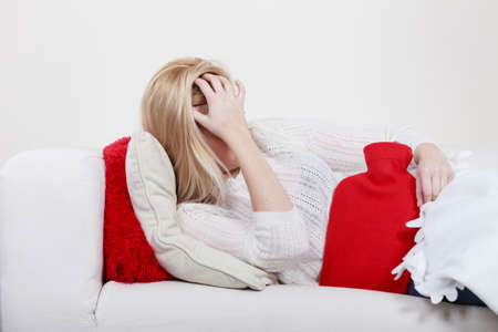 Photo for Painful periods and menstrual cramp problems concept. Woman having stomach cramps lying on cofa feeling very unwell holding hot water bottle to feel some relief - Royalty Free Image