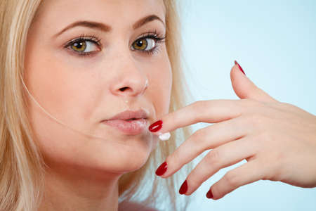 Photo for Diet, sweets temptation, delicious food concept. Woman licking whipped cream from finger or applying lip balm to dry lips, presenting her red nails - Royalty Free Image