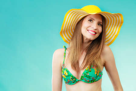 Photo for Summer holidays concept. Closeup woman in yellow hat bikini portrait on vivid blue background - Royalty Free Image