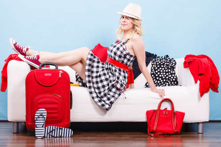 Photo for Traveling, waiting for adventure concept. Woman relaxing lying on sofa after packing clothes into her red suitcase. Indoor shot - Royalty Free Image