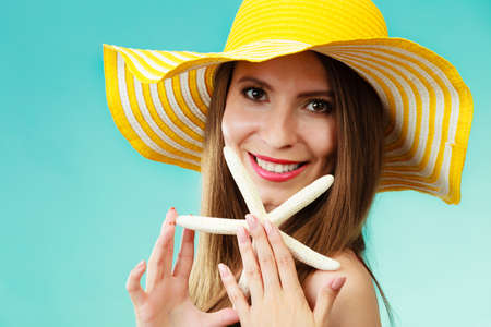 Photo for Summer holidays concept. Closeup woman in yellow hat holding white shell starfish in hand on vivid blue background - Royalty Free Image