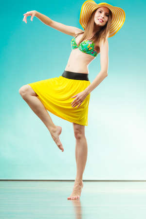 Photo for Holidays and summer fashion. Woman wearing yellow hat and bikini. Female model posing in full length on blue background. - Royalty Free Image