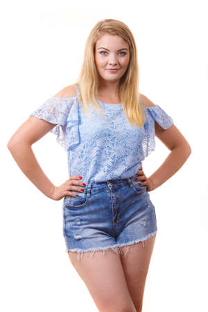Photo for Pretty joyful teen presenting fashion. Young woman wearing stylish blue top and short jeans shorts. - Royalty Free Image