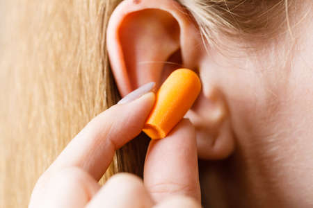 Photo pour Woman putting ear plugs into her ears getting rid on noise in loud place. - image libre de droit
