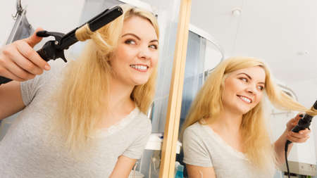 Photo for Positive young woman preparing her blonde hair, using curling pin in home bathroom. Hairdo curler creating hairstyle. - Royalty Free Image