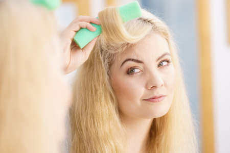 Photo pour Blonde woman using hair rollers to create beautiful hairstyle on her hairdo. - image libre de droit