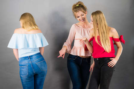 Photo for Woman being bullied by two female friends gossiping about her body shape. Friendship rivaly and envy problems. - Royalty Free Image