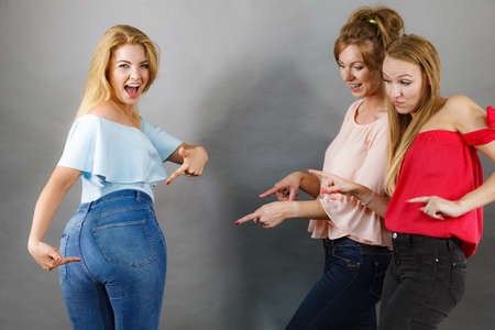 Foto de Woman wearing tight jeans showing off her curvy butt and female friends pointing at her. - Imagen libre de derechos