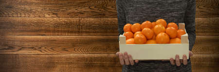 Farmer holding fresh tangerines or mandarins in wooden box in hands on wood background with copyspace. Heap of oranges, clementines or citrus fruits with place for text