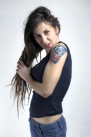 Photo pour A young female with arm tattoo holding her long hair in white wall/ portrait of girl with tatto in white wall / tattoo of a rose and skull in her arm - image libre de droit