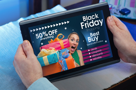 Foto de man searching website internet store to purchase gifts online in Black Friday with your tablet in you home  hands of a man at a website with an announcement concept for black friday deals - Imagen libre de derechos