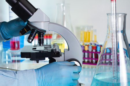 Photo for scientist looking through a microscope in the lab - Royalty Free Image