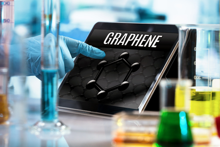 Foto de technological researcher working in the lab with screen computer and conceptual representation of graphene material / engineer working in the research laboratory with the tablet and symbol graphene in the screen - Imagen libre de derechos
