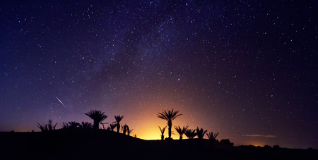 Foto de Morocco Sahara desert starry night sky over the oasis. Travelling to Morocco. Glow over the palm trees of the oasis. Billions of stars in the night sky, milky way. Panoramic photo - Imagen libre de derechos