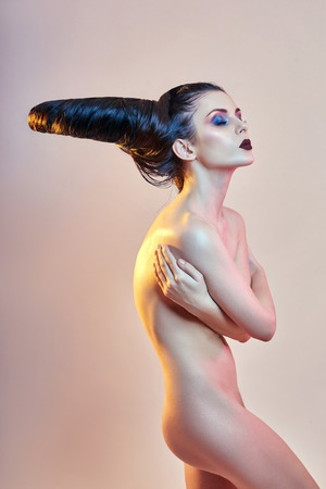 Foto de Nude art woman with hair in the form of horns, a female demon with bright makeup, perfect body girl, the horns on the head. Devil in feminine guise, Halloween. Hairstyle hair brunette - Imagen libre de derechos