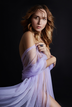 Foto de Naked woman art in lilac light transparent dress posing on a dark background. Woman wrapped in purple fabric, beautiful slim figure, purity and integrity. Luxurious Nude naked woman - Imagen libre de derechos