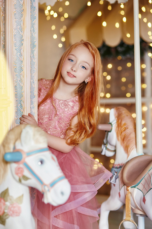 Photo pour Beautiful red-haired girl with long hair and blue eyes rides a carousel in a long pink dress. Carousel in the form of horses, redhead girl celebrates her birthday in the amusement Park - image libre de droit