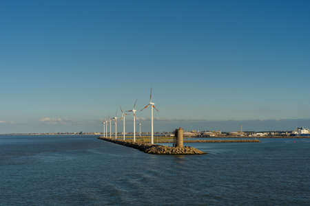 Photo pour Wind turbines near a harbor in the industrial area of Zeebrugge - image libre de droit