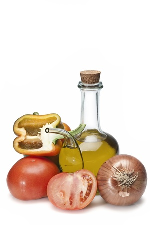 Olive oil and some vegetables like tomatoes, peppers and onions to make gazpacho isolated over a white background.