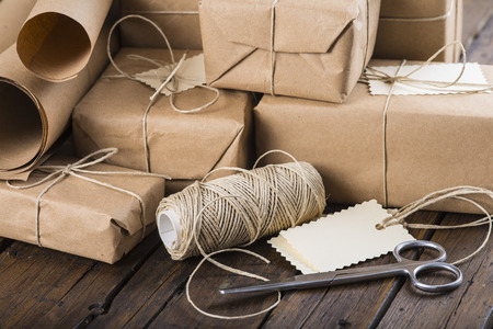 Foto de Gifts for Christmas packaged and wrapped on a wooden table - Imagen libre de derechos