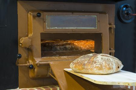 Foto de Traditional wood oven in a bakery and a baker´s shovel with a loaf - Imagen libre de derechos