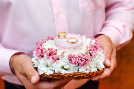 Photo for Groom holding flowers bouquet with two wedding rings - Royalty Free Image