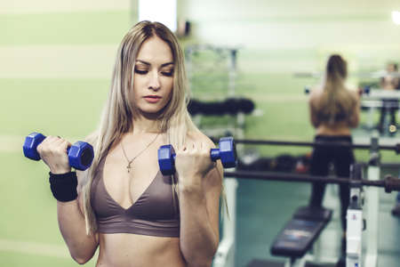 Photo for Young blonde woman doing exercises with dumbbells in a GYM. Healthy lifestyle concept. - Royalty Free Image
