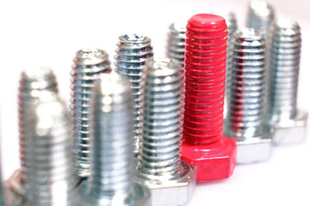 Foto de Close-up of pink bolt n a group of galvanized metallic screws. Not like everyone else, originality concept. Stainless steel bolts isolated on white background. - Imagen libre de derechos