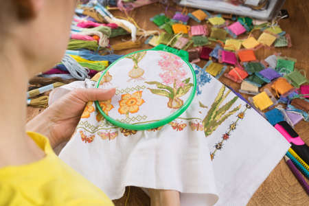 Foto de Girl sitting at a table where everything is necessary for embroidery, embroiders a big picture. Copy paste. - Imagen libre de derechos
