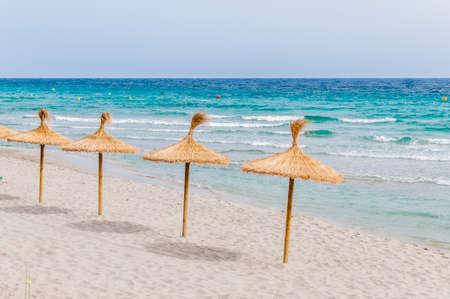 Foto de Straw umbrellas on sand beach and clear sky. - Imagen libre de derechos