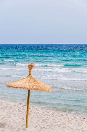 Foto de Straw umbrella on sand beach and clear sky. - Imagen libre de derechos