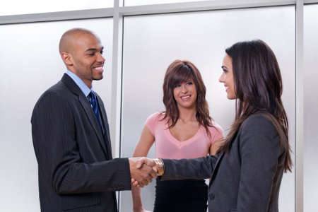 Business team of three, man and woman shaking hands.
