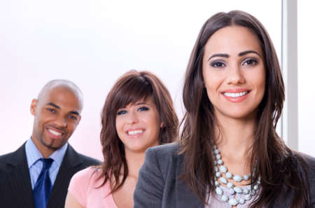 Young and successful business team, three smiling people of different races.