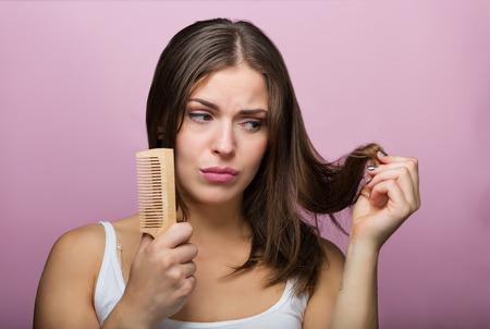 Foto de Woman brushing her hair with a wooden comb - Imagen libre de derechos