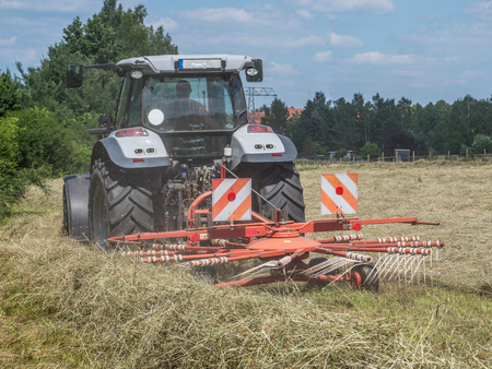 Photo pour Tractor turning hay in a field - image libre de droit
