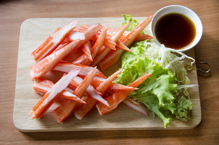 Photo for Crab sticks sashimi served with sauce and wasabi and vegetable on wooden plate in restaurant of Thailand - Royalty Free Image