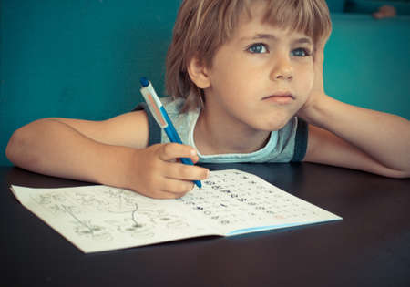Photo for Five year old boy dreaming while doing his math homework - Royalty Free Image