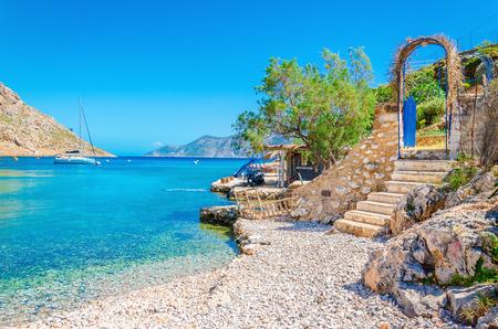 Foto de Stairs from sandy beach of amazing bay on Greece island Kalymnos, Greece - Imagen libre de derechos