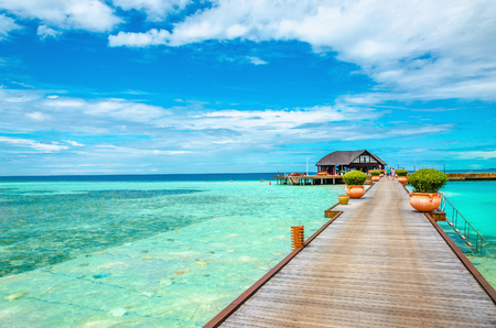 Photo for Wooden bridge leading to an exotic bungalow on the background of azure water, maldives - Royalty Free Image