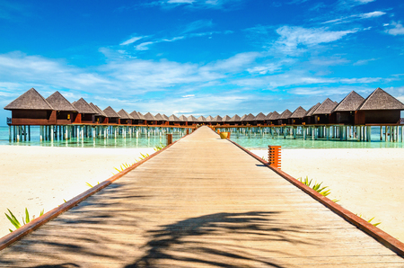 Photo pour Wooden bridge leading to an exotic bungalow on the background of azure water, maldives - image libre de droit
