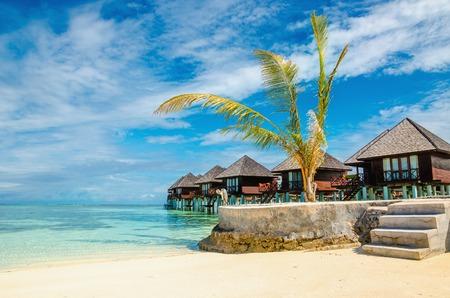 Photo pour Amazing wooden bungalow on turquoise water - image libre de droit