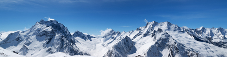Photo for Panoramic view of snow-capped mountain peaks with mount Dombay-Ulgen and beautiful blue sky with clouds at sun windy day. Caucasus Mountains in winter, region Dombay. - Royalty Free Image