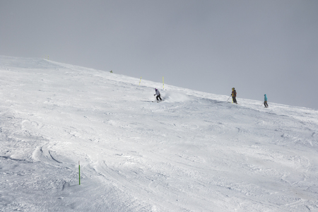 Skiers downhill on snowy ski slope and sky in fog at gray winter day before snow storm. Georgia, region Gudauri. Caucasus Mountains, Mount Kudebi.