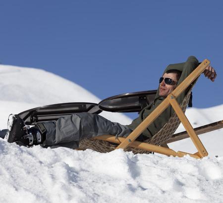 Foto de Skier at winter snowy mountains resting on sun-lounger at sunny day. Caucasus Mountains, Georgia, region Gudauri. - Imagen libre de derechos
